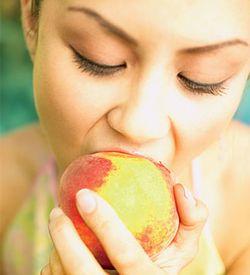 Девушка ест персик